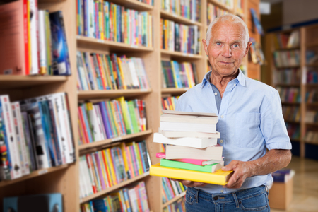 Portrait of elderly male buyer with pile of literature books in bookshop Foto de archivo