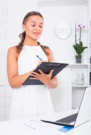 portrait of young american  woman in formal wear having clipboard in hands in office