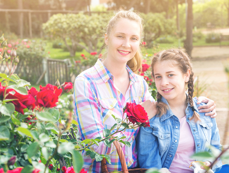 happy russian woman and teen holding a basket and standing in the park of roses. Stock Photo