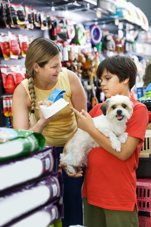 Portrait of boy with  little dog and mother looking  accessories  for pet in shop Фото со стока