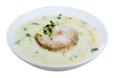 Delicious soup with smoked haddock, potatoes and onions served with greens in white bowl - traditional dish of Scottish cuisine. Isolated over white background