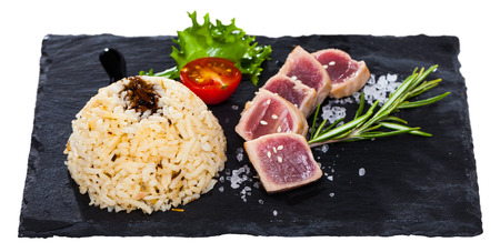 Image of  deliciously lightly fried tuna with rice, served  with greens and tomatoe. Isolated over white background