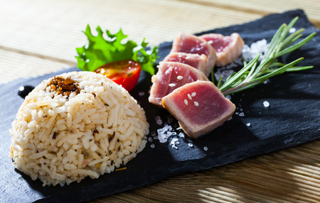 Lightly seared tuna tataki steak with garnish of steamed rice and vegetables