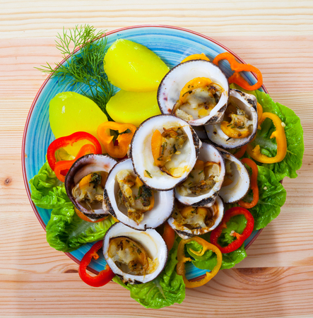 Top view of baked in oven European bittersweet clams served with boiled potatoes, fresh vegetables and greens on wooden background