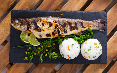 Top view of baked whole trout with rice, grilled onions, greens, canned peas and lime on black serving board