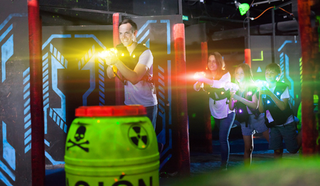 Group of happy kids and adults having fun on dark lasertag arena in colorful beams of laser guns 免版税图像