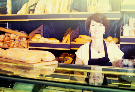 Portrait of positive female baker with fresh bread smiling in bakery 스톡 콘텐츠
