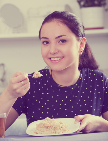 Young woman starting day with low calorie breakfast and smiling