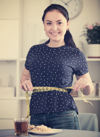 Young woman feeling happy measuring her waist at home before eating