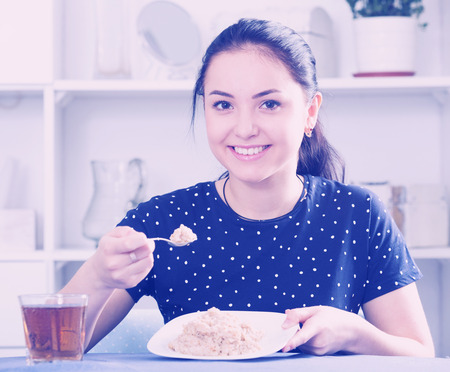Young smiling girl sitting at table and eating cereal for breakfast Reklamní fotografie