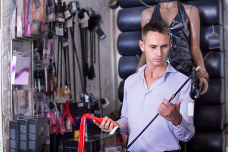 Portrait of adult man selecting bdsm toys in sex shop Archivio Fotografico
