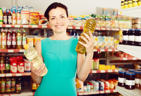 Young female in the supermarket want to buying bottle of oil
