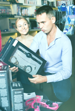 Young cheerful adult couple buying sex accessories in shop for adults