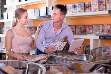 Cheerful family couple selecting erotic video in shop and smiling