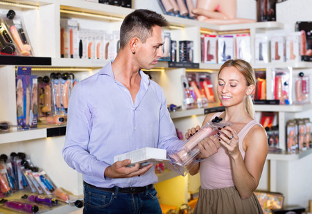 Portrait of adult positive glad  couple choosing erotic toys in sex shop Stockfoto