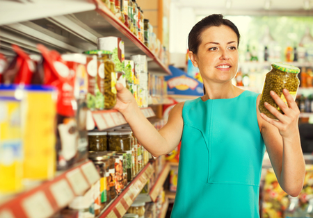 Portrait of positive female in the shop holding a preserved jar of green peas Stock Photo