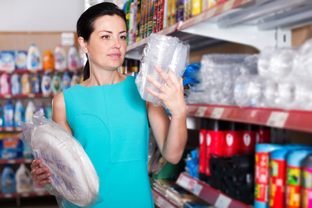 Young woman choosing plastic plate and cup at the supermarket
