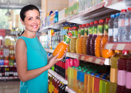 Woman is holding bottle with juice in the shop.