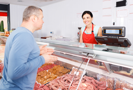 smiling  seller helping attentive male customer choosing different sausages in butcher's shop Stock Photo