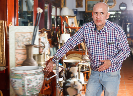 Cheerful man carefully examining antiques in store Stockfoto