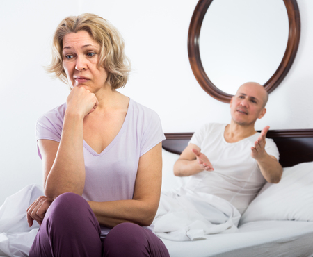 Stressed aged man and frustrated elderly woman sorting out relationships in bed