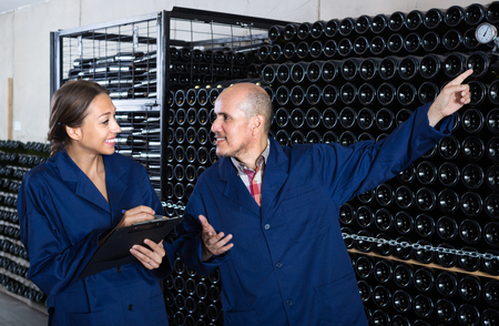 Smiling young woman with cardboard standing with male worker in small winery cellar Stock Photo