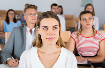 Intelligent girl listening with attention during classes in auditorium among her fellow students