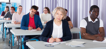 Portrait of attentive adult students on training session in auditorium