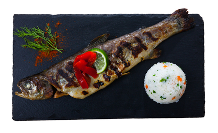 Delicious baked trout fish served on black board with garnish of white rice, grilled bell pepper, dill and lemon slice. Isolated over white background