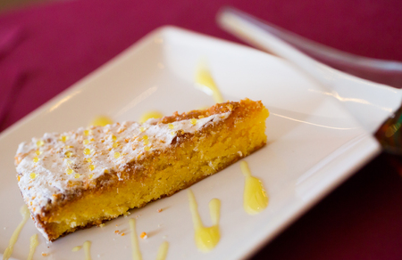 Piece of traditional Spanish almond cake Tarta de Santiago on white plate