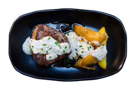 Top view of veal sirloin steak served on black plate with potato wedges and mushroom sauce. Isolated over white background Stock Photo