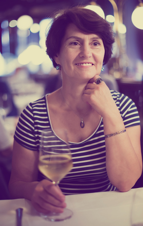 Positive mature woman sits at table at restaurant and holds glass with wine