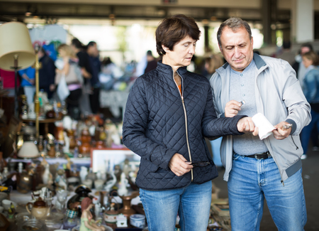 thoughtful mature spouses buying retro handicrafts on indoor flea market
