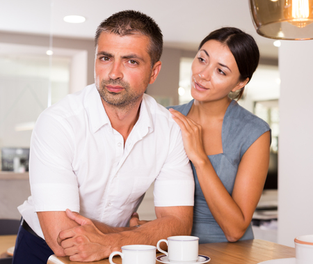 Tender loving young woman calming distressed husband in home kitchen Archivio Fotografico