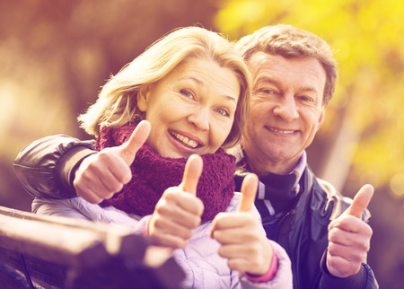 Portrait of happy elderly couple with thumbs up in spring Фото со стока