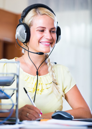 Cheerful young woman with headset working at laptop in  office Stock Photo