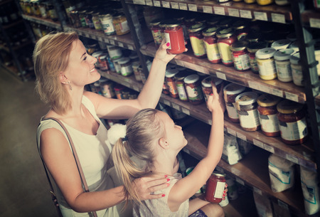 Portrait of smiling positive woman and cheerful  girl buying conserve tomato sauce in glass jar in grocery shop Zdjęcie Seryjne