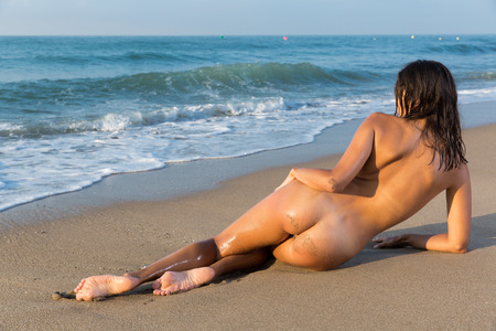 Nude girl lying on one side back to viewer on beach against sea