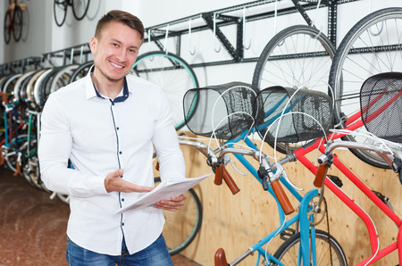 guy is shopping and choosing new bicycle with bike characteristic in bike store.