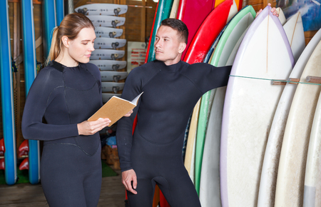Young man and woman dressed surfing suits checking surfboards on racks at the surf club. Focus on both persons Stock fotó - 109493649