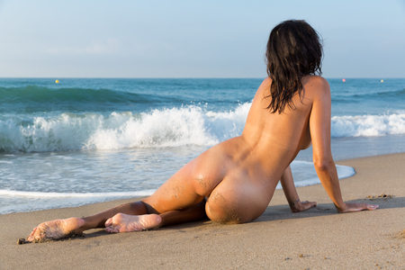 Seductive nude young girl playfully posing back on the sand at sea shore