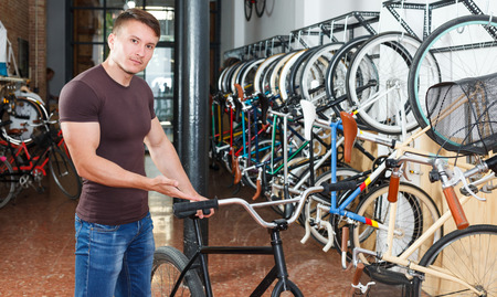 Portrait of male who is standing smile with bicylce in the bike store.