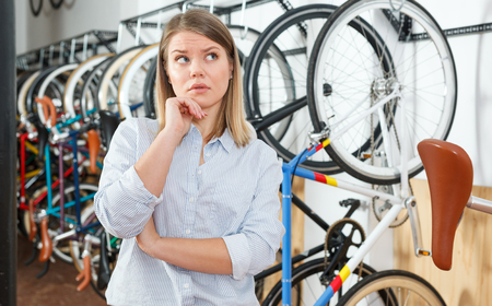 young buyer woman is standing dissatisfied in the bike store.