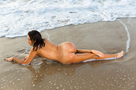 Back view  of nudity sexy girl playfully posing with  on the sandy beach