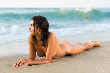 Nude girl lying on stomach in graceful pose on sand beach against sea Stock Photo