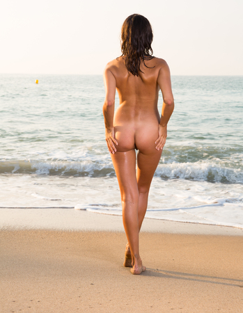 Nude slender girl standing back to viewer on beach against azure sea