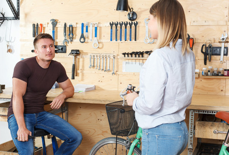 Male is consultating attractive young female about her bicycle in workshop. Reklamní fotografie