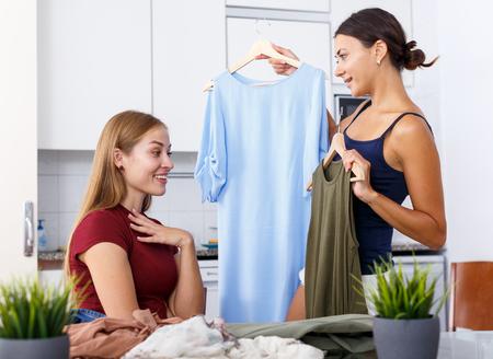 Deux amies se manifestant et essayant des vêtements à l'intérieur de la cuisine