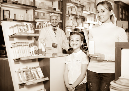 cheerful adult pharmacist standing with a cash desk in the pharmacy and helping customers