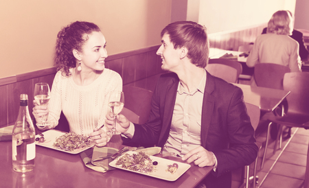 Happy man and girl chatting as having date in restaurant